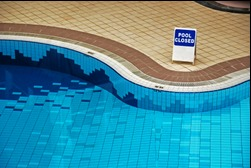 swimming pool and deck with a pool closed sign