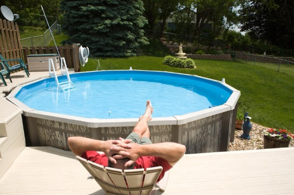 Man relaxing beside above ground swimming pool