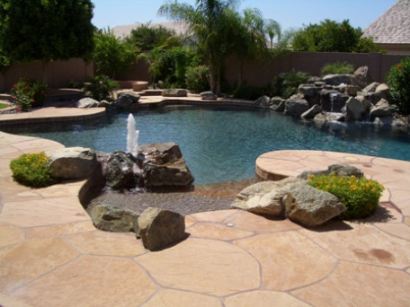 Freeform backyard swimming pool wiht fountain, waterfalls and heatsavr, liquid pool cover