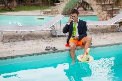 man sitting beside swimming pool