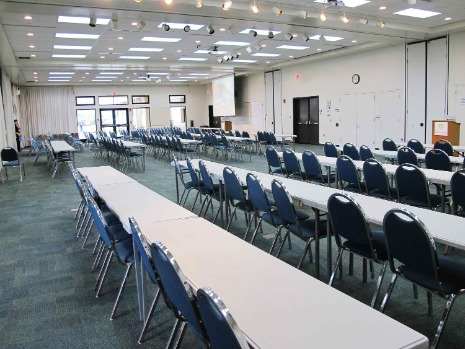 large conference room with projector screen, podium, long tables and chairs