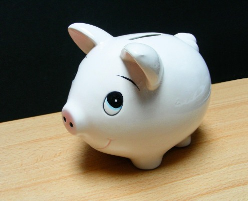 White ceramic piggy bank on a wooden table top.