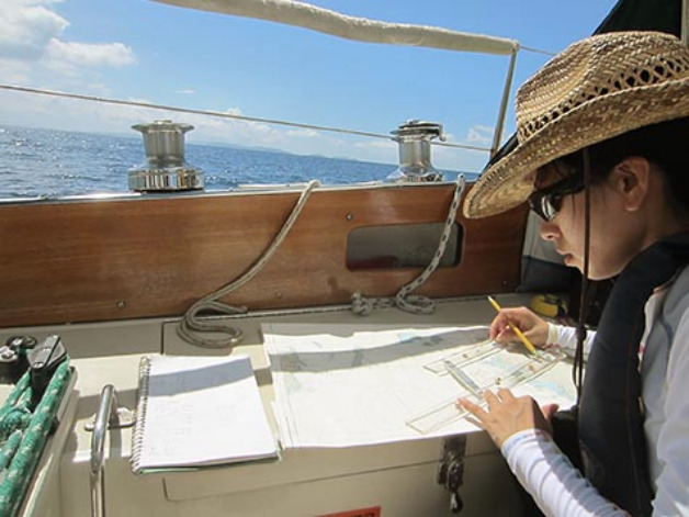 Woman wearing had and dark sunglasses charting navigation on the deck of a boat.