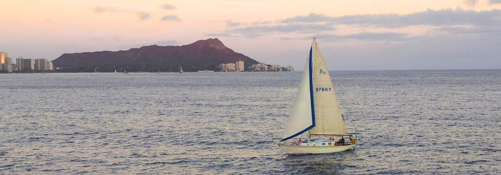 Sail boat at sunset with Diamond Head in the background.