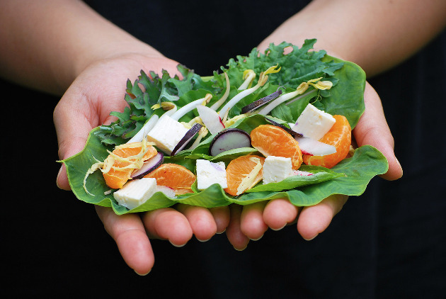 Hands holding a large green leaf with orange slices, tofu and vegetables.