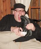 Nick Logue, caucasian man with dark hair wearing glasses pretending to bite a shoe.