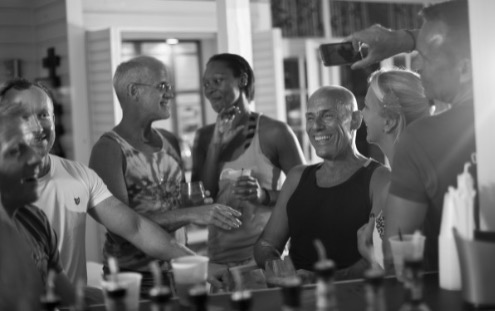black and white photo of a group of men and women laughing at a bar at alexanders guesthouse