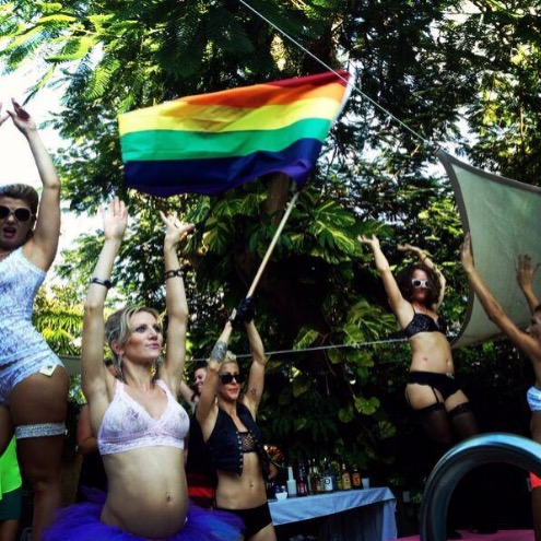 candid shot from womanfest event, woman waving rainbow flag