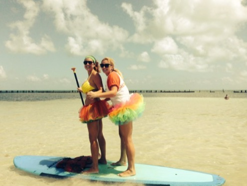 two women in tutus on a paddleboard at the beach
