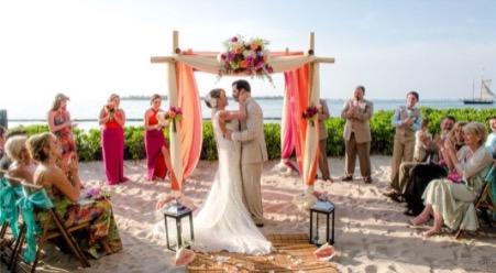 couple during wedding ceremony at pier house resort & spa on beach under ceremony arch