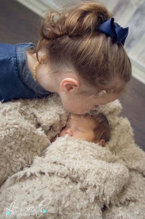 newborn photography siblings kissing head