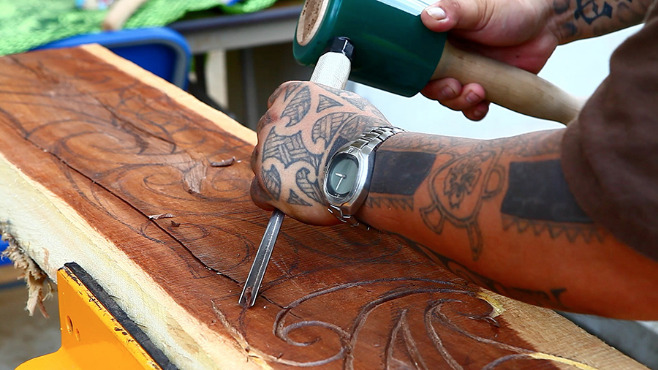 Man with chisel and hammer doing wood carving